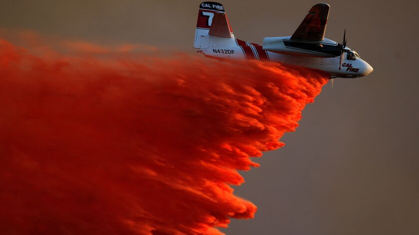SAN MARCOS, CA.-MAY 14, 2014: A Cal Fire airplane makes a fire retardant drop on brush near Cal Sta