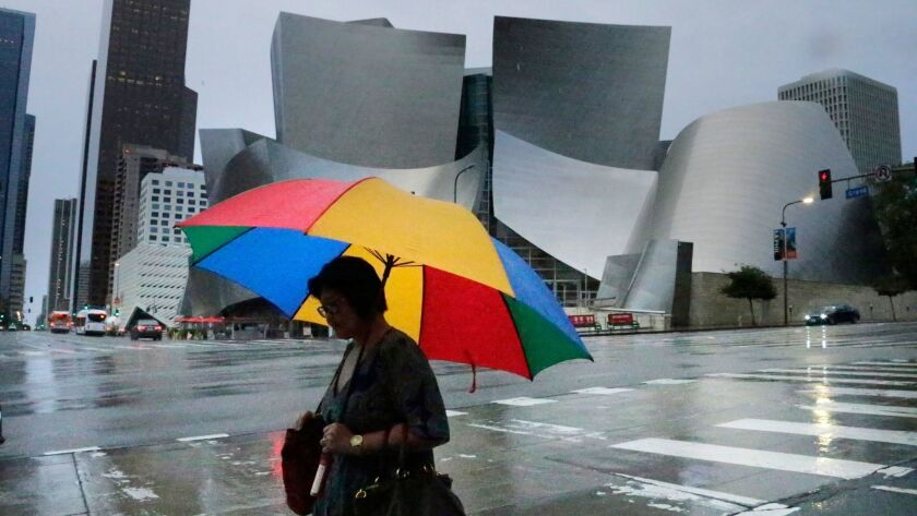 Roads are glistening in morning rain and umbrellas are out in downtown Los Angeles as the first of two storms hits the Southland.