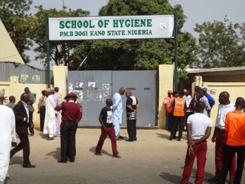 Policemen and others stand in front of the public health college in the northern Nigerian city of Kano where a bomb blast on Monday killed at least eight people.