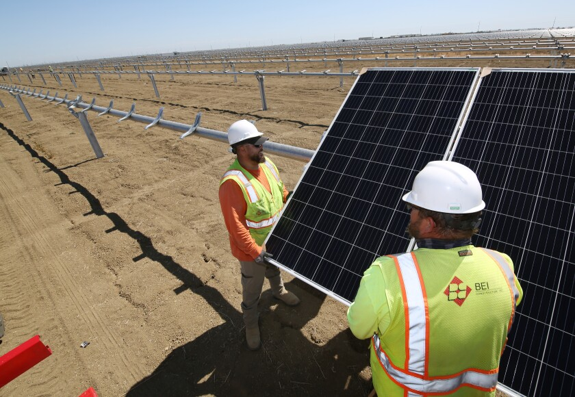 Workers place panels at the construction site of Westlands Solar Park in California's San Joaquin Valley.