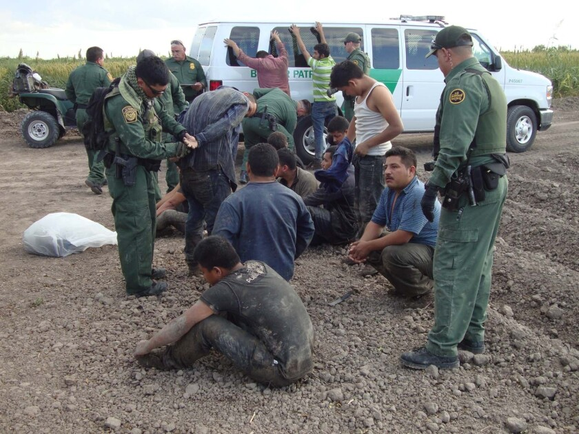 Texas Border Patrol agents detain migrants crossing into the U.S. illegally. An agent fired several shots toward an armed militia member during the course of a pursuit near the border on Friday.