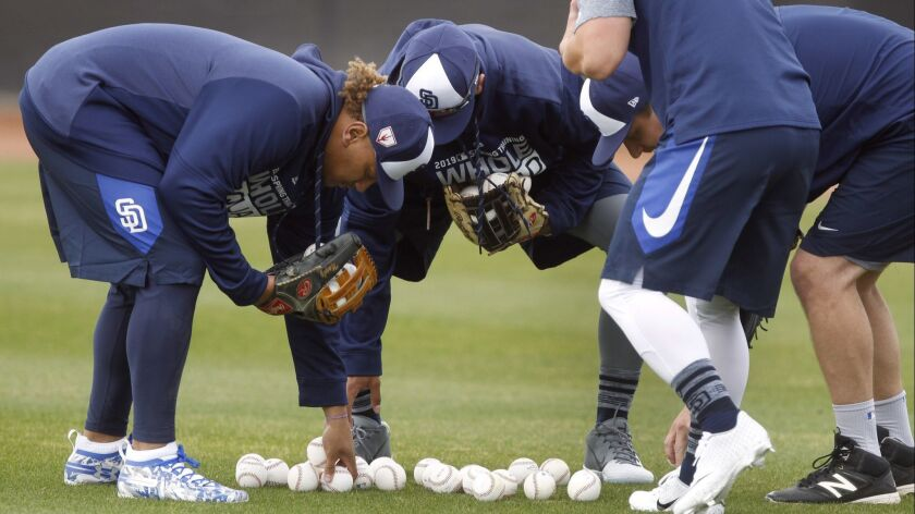 PEORIA, February 13, 2019   Padres players pick up baseballs during Padres spring training for pitch