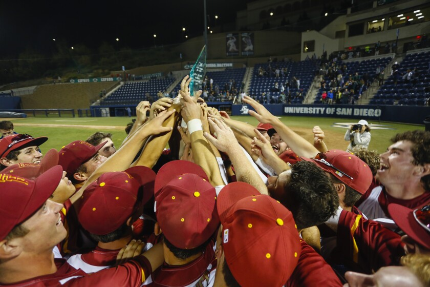 The Torrey Pines Falcons hoist their trophy after their extra innings win over Poway in the Open Division championship.