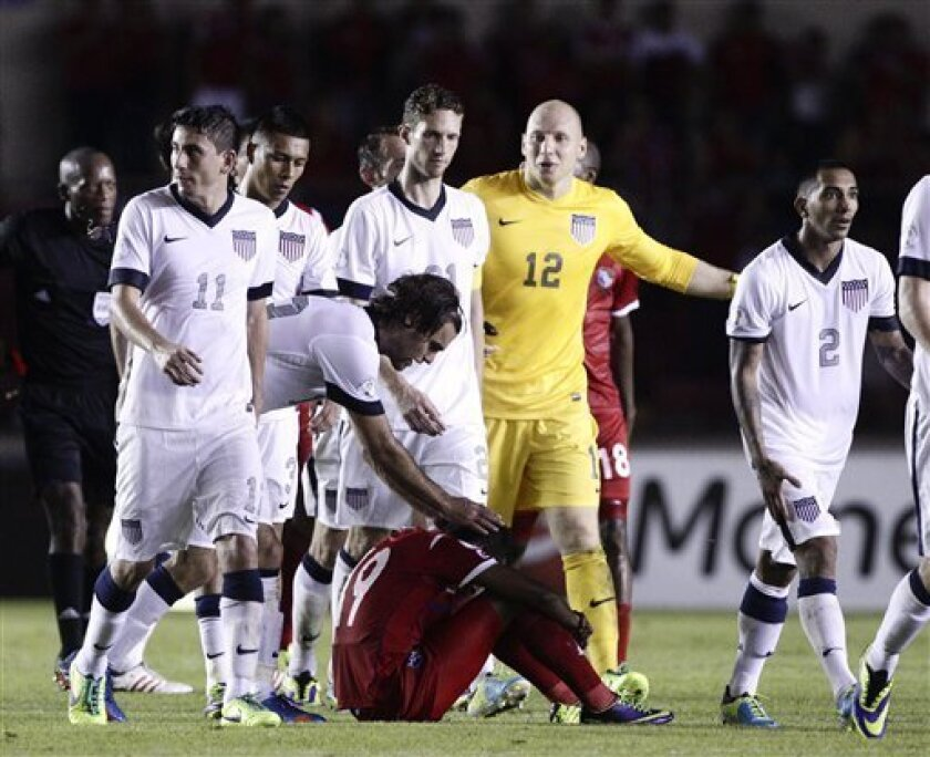 Graham Zusi of the U.S. reaches out to a dejected Alberto Quintero of Panama after the U.S. defeated Panama in a 2014 World Cup qualifying soccer match in Panama City, Tuesday, Oct. 15, 2013. The United States rallied for a 3-2 win at Panama on Tuesday night that left Mexico's World Cup hopes alive