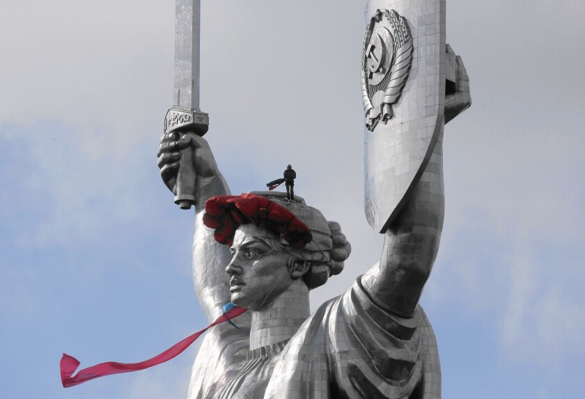 A worker installs a wreath of poppies and ribbon on the Mother Motherland monument in Kiev, Ukraine, on May 8 to mark the anniversary of the Nazis' World War II defeat. The statue may lose the Soviet seal on its shield.