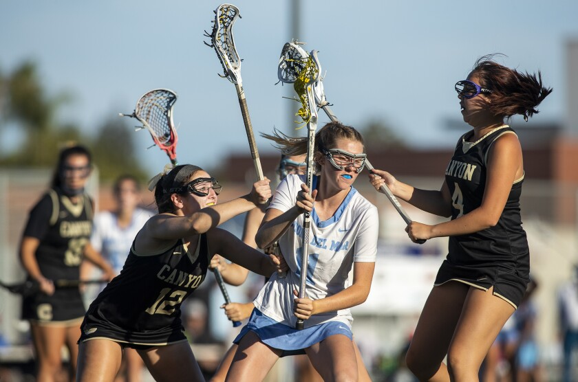 Corona del Mar's Abby Grace, center, battles with Canyon's Lindsay Parsons, left, and Calle Bandong.