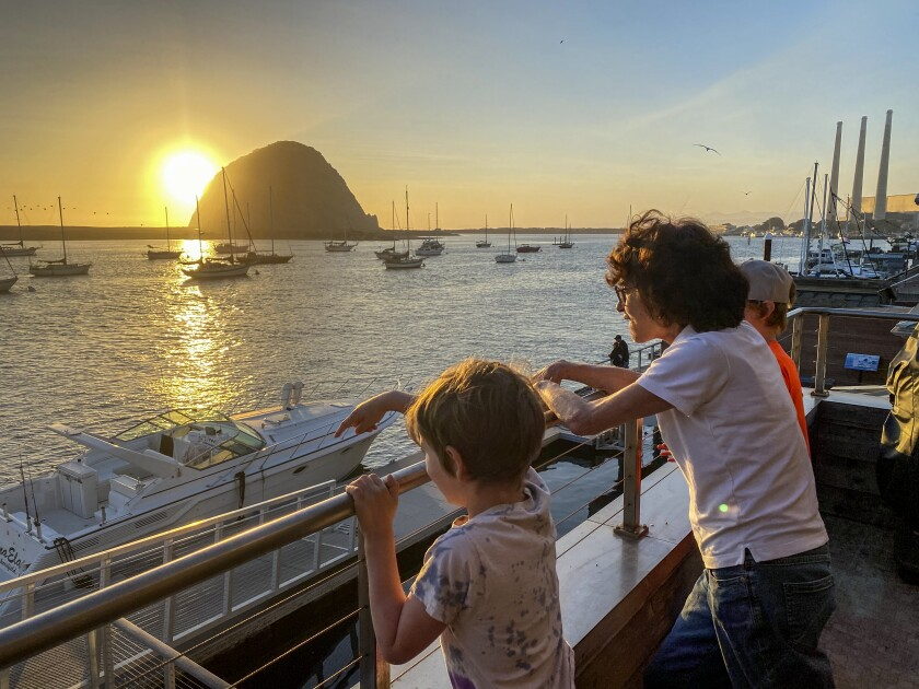 Visitors take in the sunset over Morro Bay.