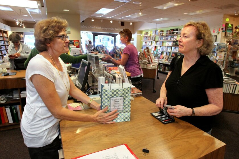 Local author Kay Sanger, at right, buys books at Warwick's in La Jolla. Assisting her is employee Janet Lutz, at left. Booksellers have suffered because of competition from Amazon.com, in part because they have to collect sales tax and online retailers don't. A state law that takes effect Saturday will change that.