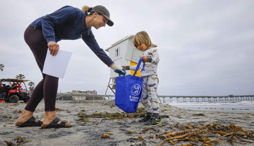 Surfrider Foundation San Diego County Chapter volunteers Liz Lawrence, left, and her son, 31/2-year-old Reed Phillips, right, pick up trash left on the beach near the Ocean Beach Pier, July 5, 2019, in San Diego, California from Fourth of July revelers. Ocean Beach was one of five San Diego County locations for the Surfrider Foundation cleanup. Liz said a lot of the trash was remnants of fireworks.