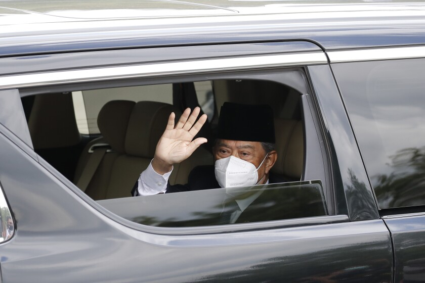 Embattled Malaysian Prime Minister Muhyiddin Yassin waves from a car while entering the National Palace to meet with the King in Kuala Lumpur, Malaysia, Monday, Aug. 16, 2021. Muhyiddin arrived at the palace for a meeting with the king Monday, where he is expected to hand in his resignation after conceding he didn't have majority support to rule. (AP Photo/FL Wong)