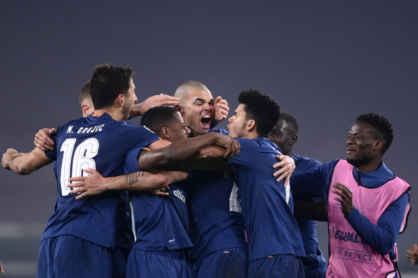 Porto players celebrate after the during the Champions League, round of 16, second leg, soccer match between Juventus and Porto in Turin, Italy, Tuesday, March 9, 2021. (Fabio Ferrari/LaPresse via AP)