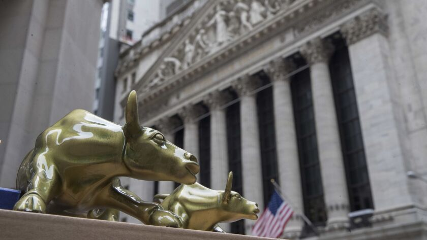 "Small replicas of Arturo Di Modica's ""Charging Bull"" statue are for sale on a street vendor's table outside the New York Stock Exchange."