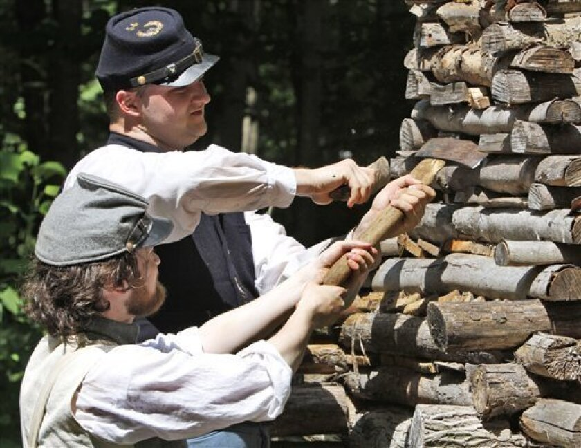 In a June 18, 2011 photo, Confederate Civil War re-enactor, Trystan Bennett, bottom, of Fredericksburg, Va., and Union re-enactor David Cauffield, of Charlottesville, Va., work on a chimney during a period re-enactment of Civil War hut construction at Montpelier in Orange, Va. Fearing that they'll only get one chance to make the most of the sesquicentennial fever, some historic sites are conducting the 150th anniversary Civil War re-enactments this year rather than waiting, making a big deal out of their 147th or 148th anniversaries instead. (AP Photo/Steve Helber)
