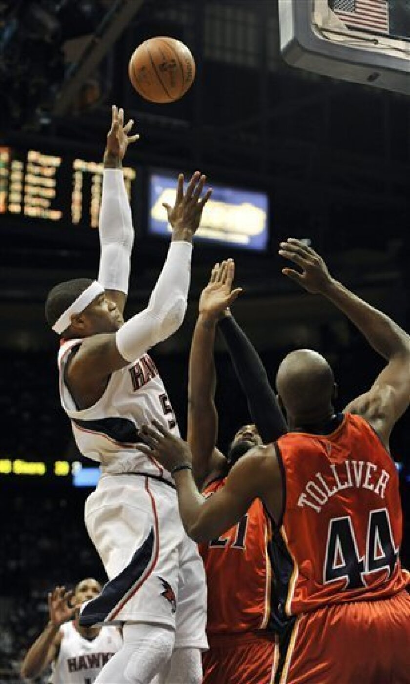 Atlanta Hawks forward Josh Smith (5) takes a shot against Golden State Warriors center Ronny Turiaf (21) and Warriors forward Anthony Tolliver (44) during the first quarter of an NBA basketball game at Philips Arena, Friday, March 5, 2010, in Atlanta. (AP Photo/Gregory Smith)