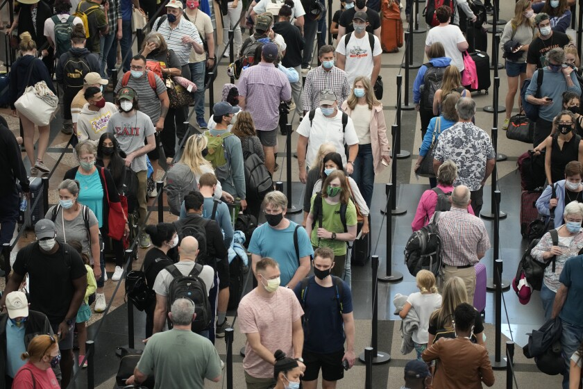 Travelers make their way through the north south security checkpoint at Denver International Airport Friday, July 2, 2021, in Denver. (AP Photo/David Zalubowski)