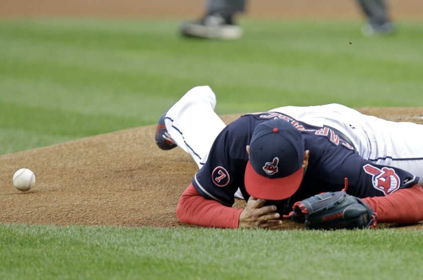 Cleveland Indians relief pitcher Carlos Carrasco falls to the ground after being hit with a line drive by Chicago White Sox's Melky Cabrera during the first inning of a baseball game Tuesday, April 14, 2015, in Cleveland. (AP Photo/Mark Duncan)