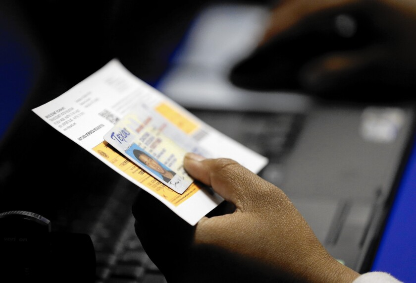 A Texas election official checks a voter's ID at an early voting location in Austin last month.