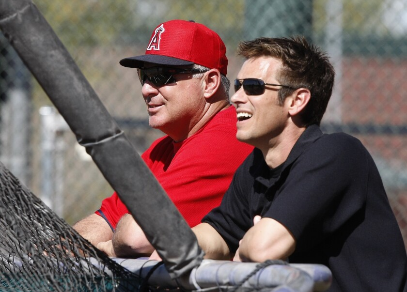 Angels Manager Mike Scioscia and General Manager Jerry Dipoto talk during spring training in 2014.