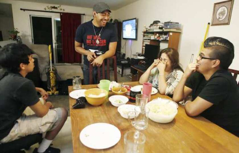 Israel, 14, from left, Isaac, 21, Lucy, and Ruben Barrera, 18, spend time together during dinner at their home in Los Angeles. Israel is the only one documented and was born here in the United States. Israel's mother, Lucy, moved to the United States from Mexicali, Mexico in 1995 with Israel's brothers, Isaac and Ruben.