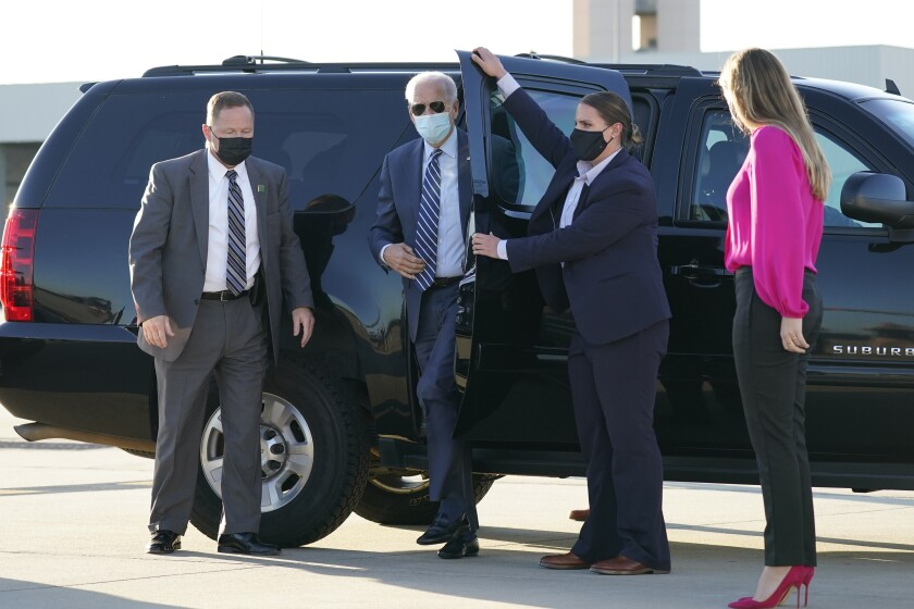 Joe Biden steps out of his van at Raleigh-Durham International Airport; granddaughter Finnegan Biden looks on.