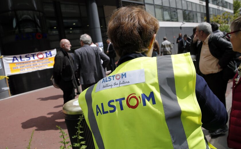 Workers gather in front of the Alstom company headquarters, the leading global maker of high-speed trains, power plants and grids, in Levallois-Perret, outside Paris, France, Wednesday, April 30, 2014. French engineering firm Alstom SA said Wednesday it was ready to accept General Electric Co.'s bid to buy its energy business, but bent to its government's order to put any deal on hold for review. (AP Photo/Christophe Ena)