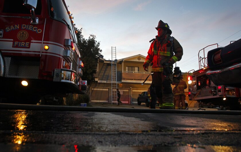 San Diego fire Capt. Kevin Lyon helps clean up after firefighters extinguished a blaze in an apartment on 38th Street in Normal Heights on Monday, March 5, 2012. No one was hurt in the fire, but a cat and dog died.