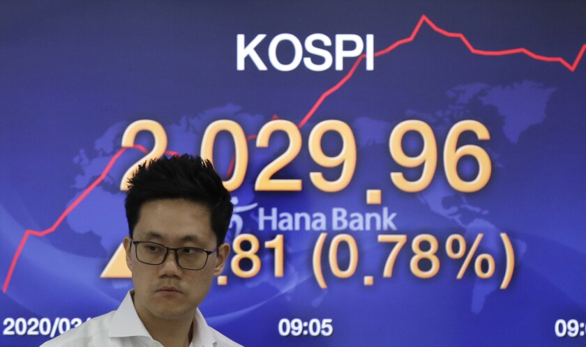 A currency trader walks by a screen showing the Korea Composite Stock Price Index (KOSPI) at the foreign exchange dealing room in Seoul, South Korea, Wednesday, March 4, 2020. Asian stock markets were mostly higher Wednesday after Wall Street sank despite an emergency U.S. interest cut aimed at defusing fears a virus outbreak might depress global economic activity. (AP Photo/Lee Jin-man)