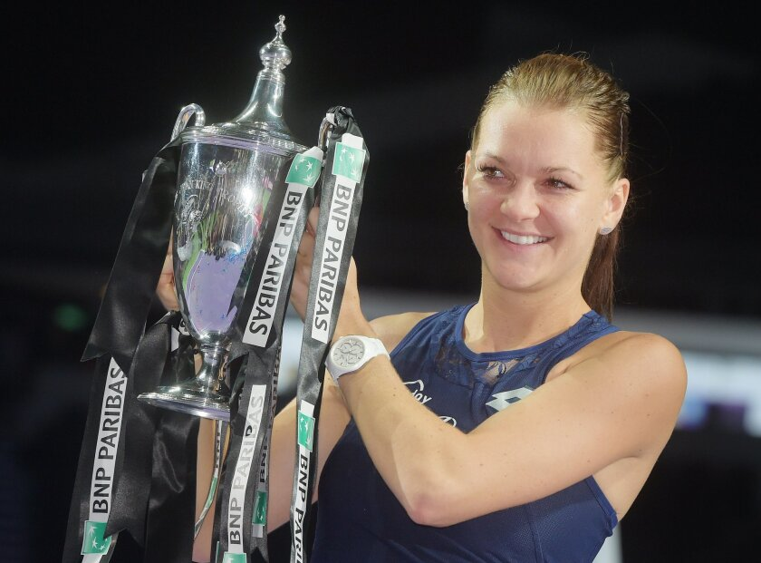 Agnieszka Radwanska of Poland poses with the trophy after she won the singles final against Petra Kvitova of the Czech Republic at the WTA tennis finals in Singapore on Sunday, Nov. 1, 2015.  (AP Photo/Joseph Nair)