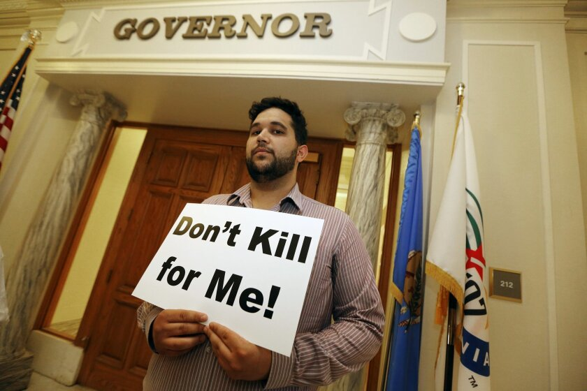 Hossein Dabiri with Oklahoma Coalition Against the Death Penalty holds a sign protesting the death penalty at the State Capitol in Oklahoma City, Tuesday April 29, 2014. Oklahoma prison officials halted the execution of an inmate after the delivery of a new three-drug combination on Tuesday failed