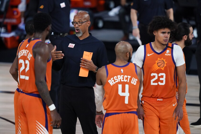 Phoenix Suns head coach Monty Williams talks with Phoenix Suns center Deandre Ayton (22), guard Jevon Carter (4) and forward Cameron Johnson (23) during the second half of an NBA basketball game Sunday, Aug. 2, 2020, in Lake Buena Vista, Fla. (AP Photo/Ashley Landis, Pool)