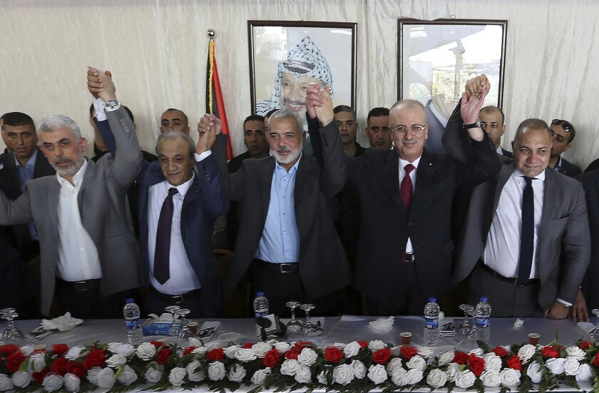 Leaders of Hamas and the Fatah-led Palestinian government join hands at a meeting on Oct. 2.