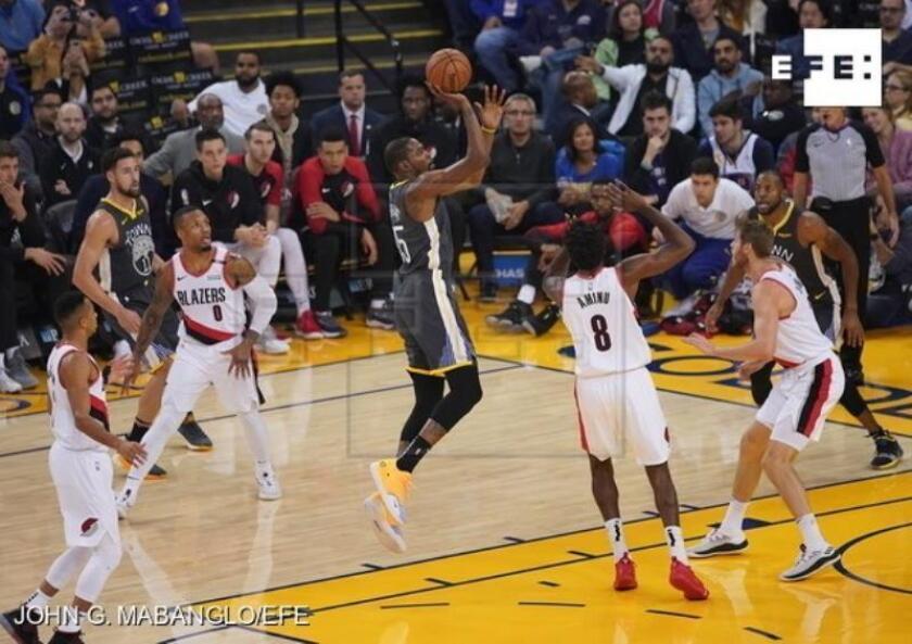 El jugador de los Golden State Warriors Kevin Durant (c) intenta encestar durante el partido disputado hoy contra los Portland Trail Blazers. EFE