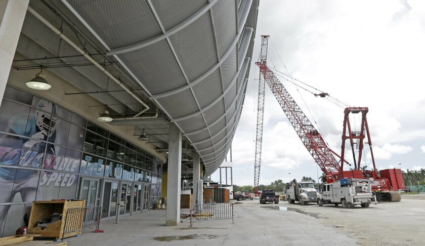 Construction equipment stands outside the Miami Dolphins' NFL football stadium Thursday, June 2, 2016, in Miami Gardens, Fla. The first game of 2016 is three months away, and the stadium is far from ready. But Dolphins officials say they're on schedule with a major renovation, thanks to crews worki