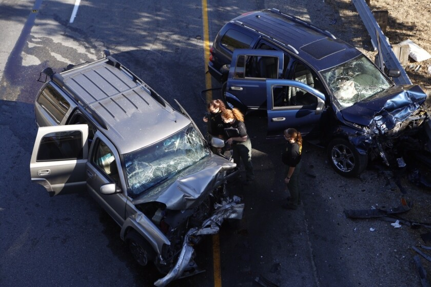 A San Bernardino County sheriff's deputy in a helicopter shot and fatally wounded a man driving a Chevy Tahoe the wrong way during a chase on the 215 Freeway in San Bernardino on Sept. 18, 2015, but the vehicle kept going and crashed head-on into a family in a Dodge Durango, right.