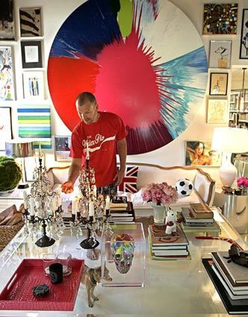 Johnson Hartig, co-designer of clothing line Libertine, lights a candelabra at the 1920s Mediterranean bungalow he renovated in Los Angeles' Hancock Park area. A huge spin-art work by Damien Hirst radiates color in the living room, dominated by an oversized Lucite table.