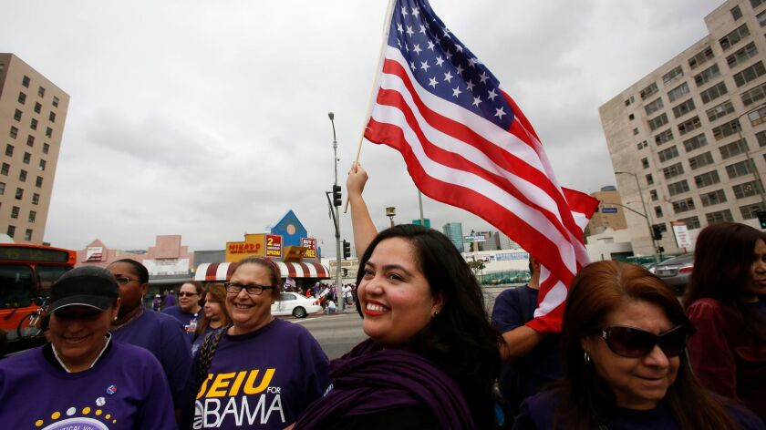 Wendy Carrillo waves a flag at a 2013 May Day march in downtown Los Angeles. (Irfan Khan / Los Angeles Times)