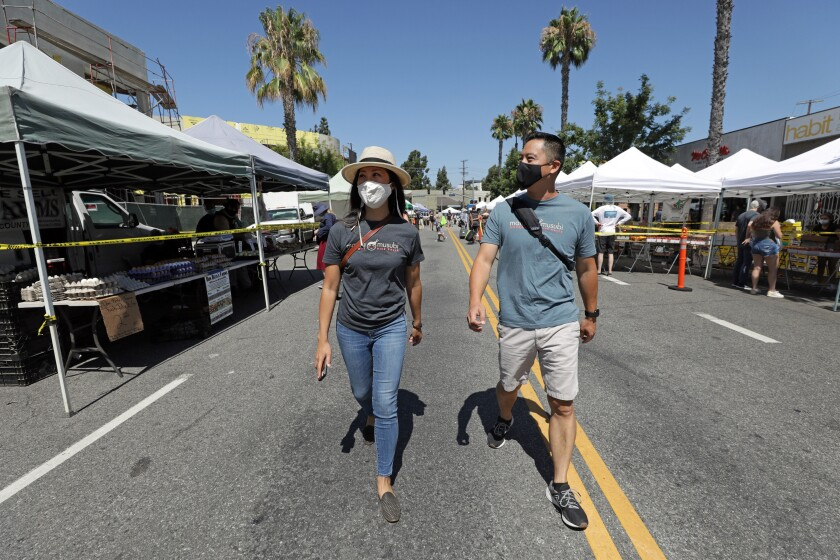Mama Musubi owners and siblings Carol and Phillip Kwan walk through the Studio City Farmers Market.
