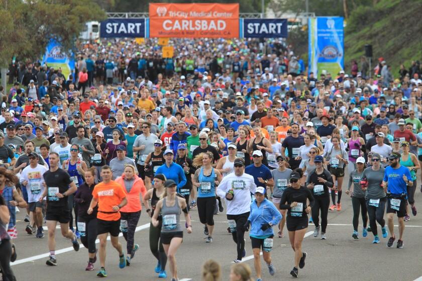 Waves of runners start the Carlsbad Half Marathon Sunday.