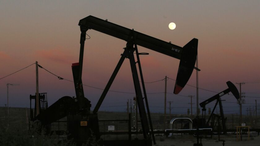 FILE - In this June 8, 2017, file photo, oil derricks are busy pumping as the moon rises near the La