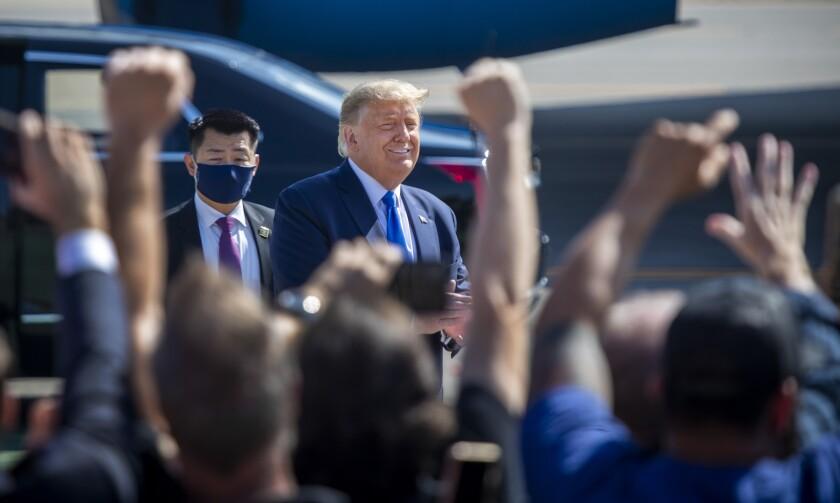 President Trump, outside at John Wayne Airport, smiles at supporters.