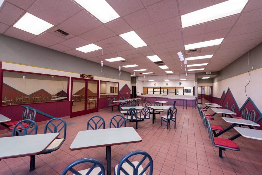 A room with drop ceilings also includes the kind of fixed furniture that is common to fast food restaurants