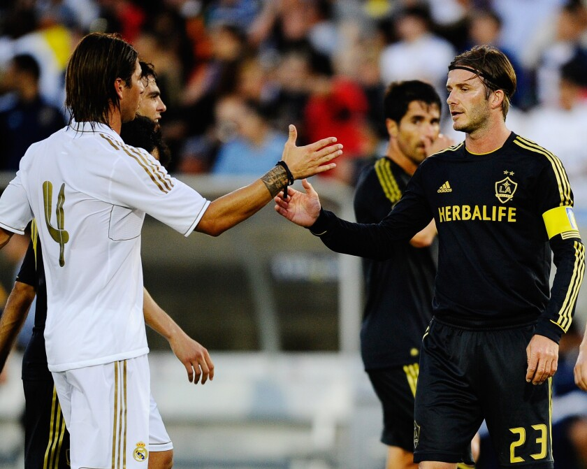 In 2011, David Beckham (23) of the Galaxy shakes hands with Sergio Ramos of Real Madrid at a match at the Herbalife World Football Challenge at the L.A. Memorial Coliseum.