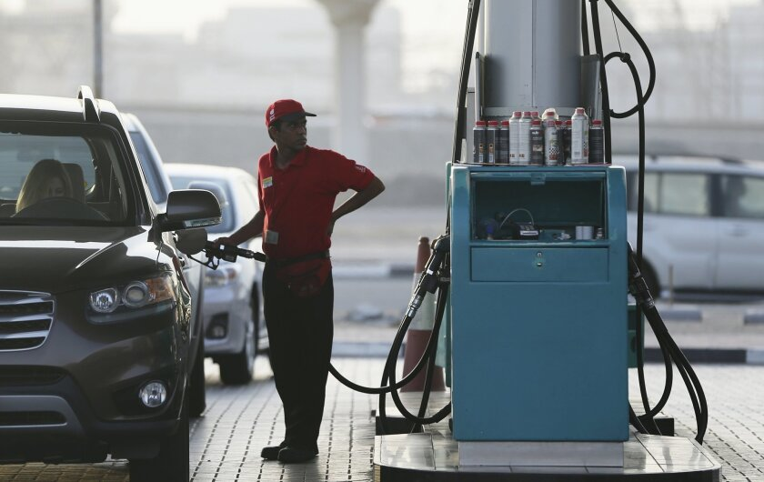 A petrol station staff member fills a gas tank on Wednesday, July 22, 2015, in Dubai, United Arab Emirates. UAE authorities plan to begin linking fuel prices to global prices starting Aug. 1. Gasoline prices are currently set by the government at subsidized rates, with a liter of regular gasoline selling for 1.72 dirhams (47 cents), or about $1.78 a gallon. (AP Photo/Kamran Jebreili)