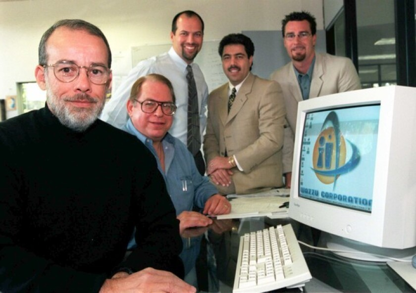 Luis Villalobos, left, started Tech Coast Angels in 1997 and was its first president. Next to him is board member Lawrence Goelman. Also shown are officials from Wazzu Corp., which the investment group aided.