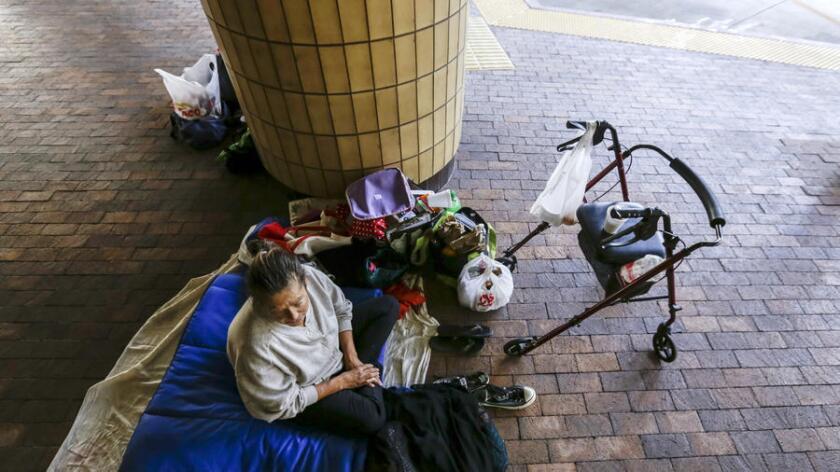 Denise Aken, de 58 años de edad, quien ha estado sin hogar hace 19 meses, descansa bajo el techo de Courtyard, la terminal de autobuses de Santa Ana que abrió recientemente sus puertas a los cientos de personas desamparadas que vivían en el Centro Cívico (Irfan Khan / Los Angeles Times).