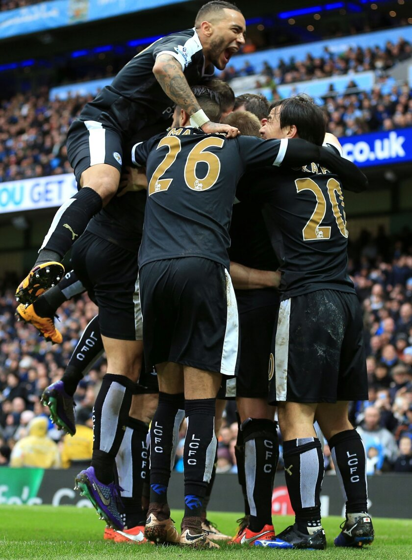 Leicester City's Robert Huth, hidden, celebrates with teammates after scoring his side's third goal of the game during the English Premier League soccer match at the Etihad Stadium, Manchester. England, Saturday Feb. 6, 2016. (Martin Rickett / PA via AP) UNITED KINGDOM OUT - NO SALES - NO ARCHIVES