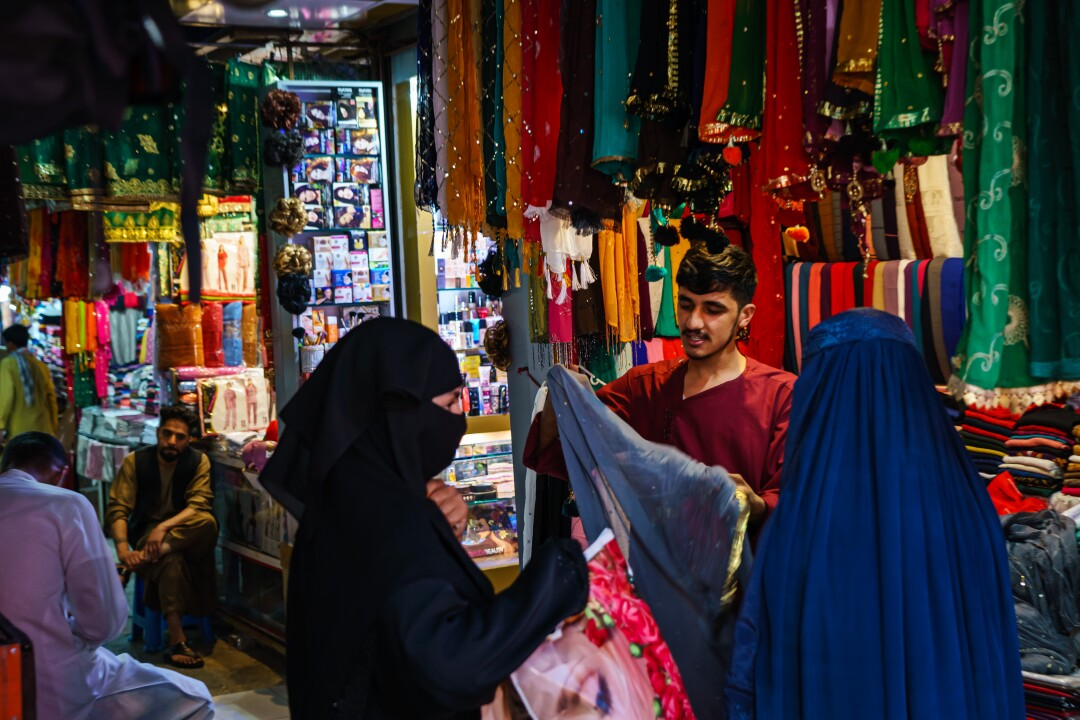 A shopkeeper shows his wares to the women shopping in the Lycee Maryam Bazaar in Kabul, Afghanistan.