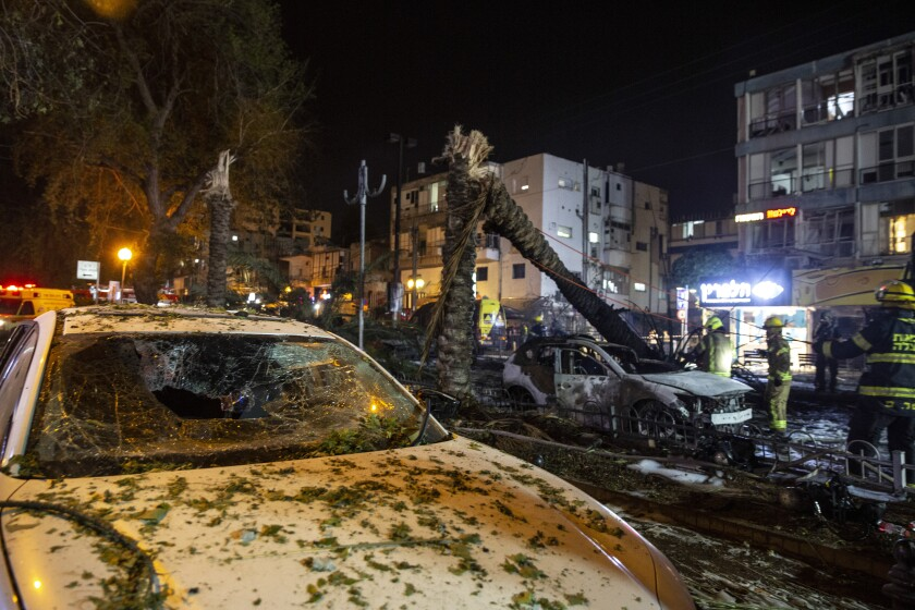 A car with a broken windshield, foreground, near other damaged cars, trees and buildings.