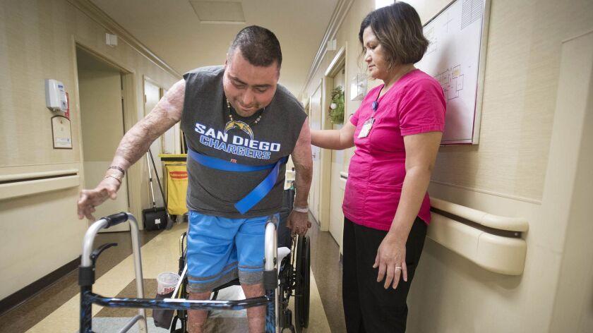 SPRING VALLEY, CA 7/3/2018: Julio Edeza, left, is assisted by Mila Fernandez, restorative nursing as