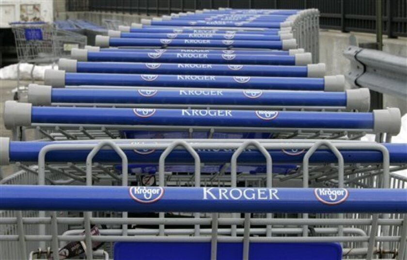 FILE - In this March 11, 2008 file photo, shopping carts are lined up outside a Kroger Co. supermarket in Cincinnati. The Kroger Co. said Tuesday, Dec. 8, 2009, it lost $875 million in its third quarter, blaming tough price competition and the struggling California economy's hit on its grocery business.(AP Photo/Al Behrman, File)